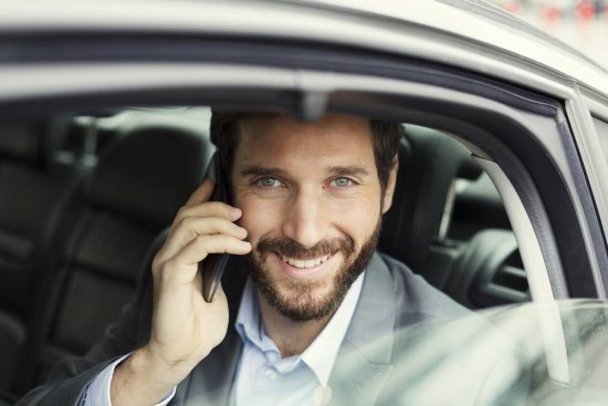 Businessman on mobile phone in rear of car Looking camera